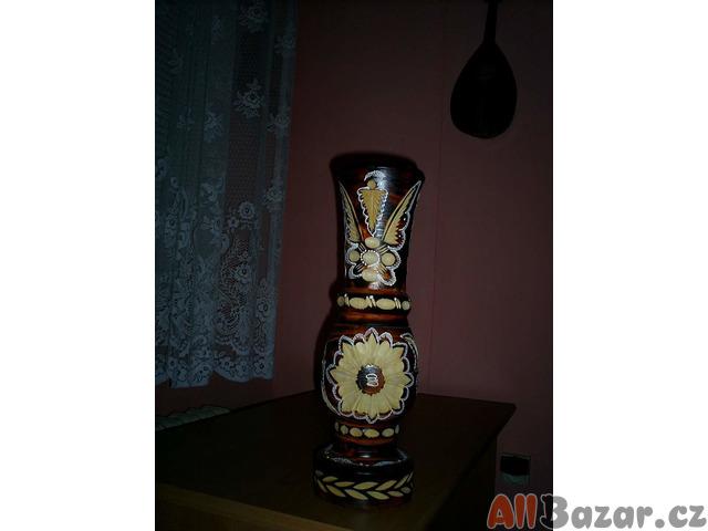 Starožitnou vázu vyrobenou a vydlabanou z kmenu stromu, ornamenty kytky. Foto.